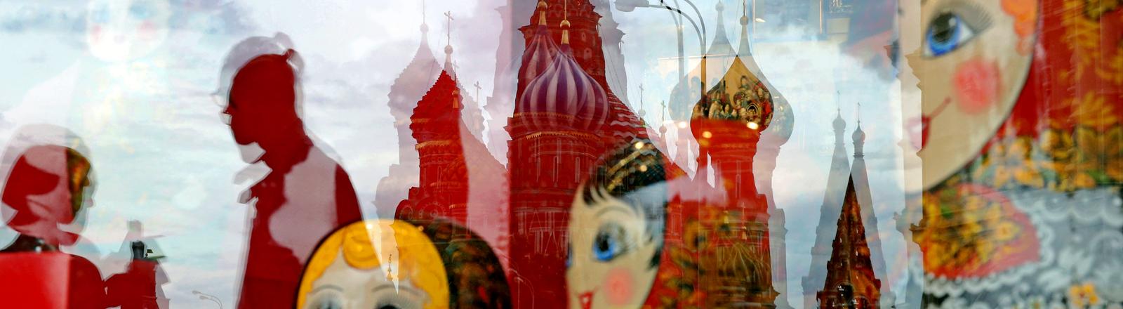 Im Schausfenster stehen Matroschka-Puppen, im Glas spiegelt sich die Basilika