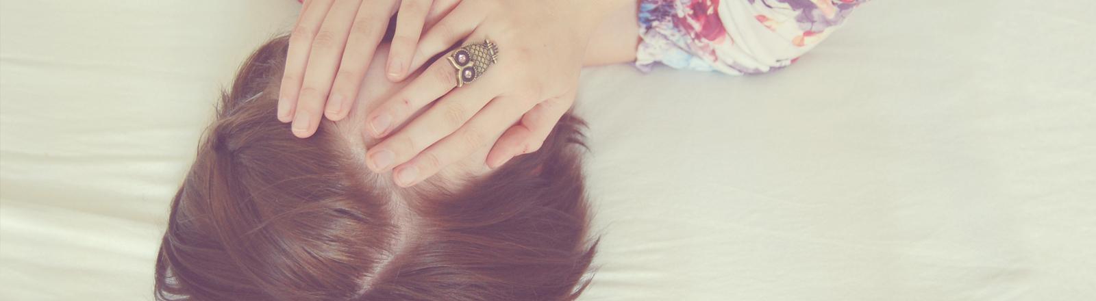 Eine junge Frau liegt auf dem Bett und hält ihre Hände vors Gesicht