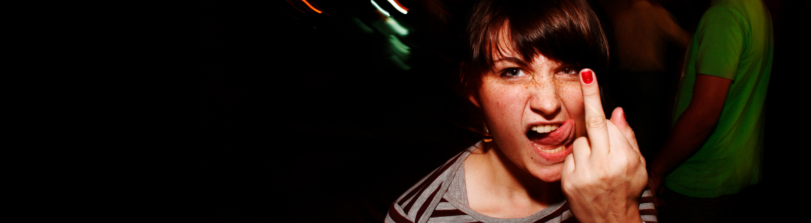 Eine junge Frau streckt den Mittelfinger in die Luft und streckt die Zunge raus
