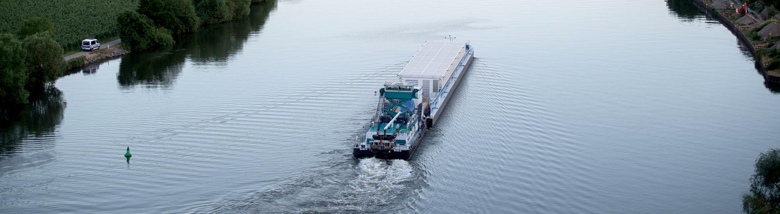 Schiff mit großen Behältern auf einem Fluss.