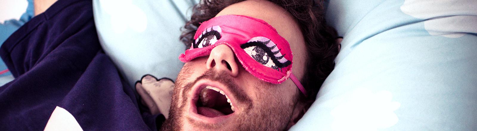 Mann liegt mit einer Schlafmaske im Bett.