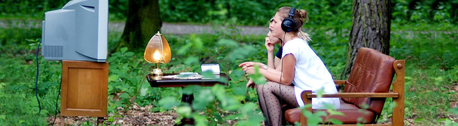 In einem Garten mit Bäumen sitzen zwei Mädchen auf einer Couch, vor ihnen ein kleiner Tisch, eine Lampe und ein Fernseher auf einem Sideboard