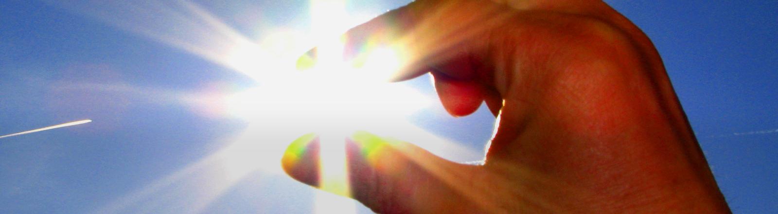 Zwei Finger scheinen die Sonne vom Himmel zu pflücken