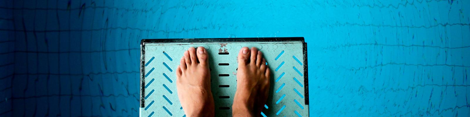 Ein Mann steht auf einem Sprungbrett - unter ihm ist der blaue Pool zu sehen
