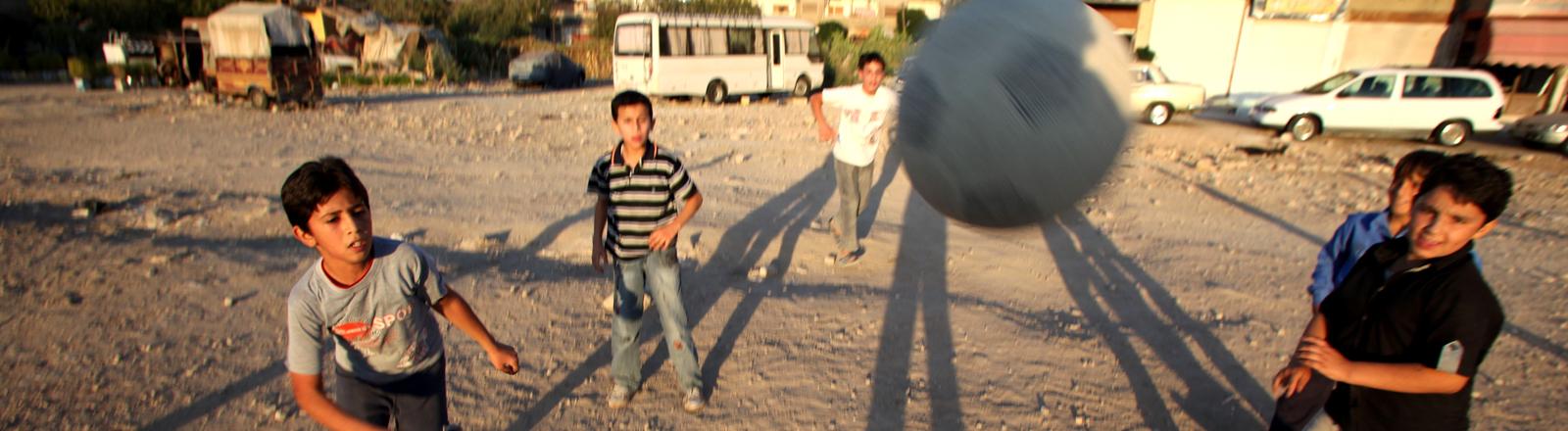 Kinder spielen Fußball in der Abendsonne auf einem staubigen Platz in Damaskus