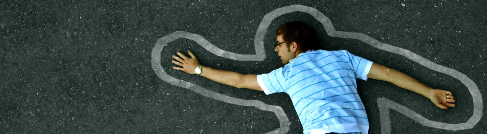 Ein junger Mann mit Brille liegt auf dem Asphalt, um seinen Körper herum ist eine weiße Linie gemalt