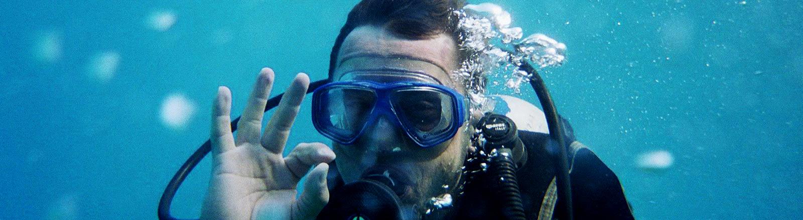 Ein Taucher macht unter Wasser das OK-Zeichen.