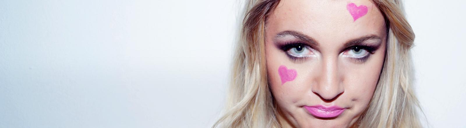Eine junge Frau hat rosa Herzchen im Gesicht