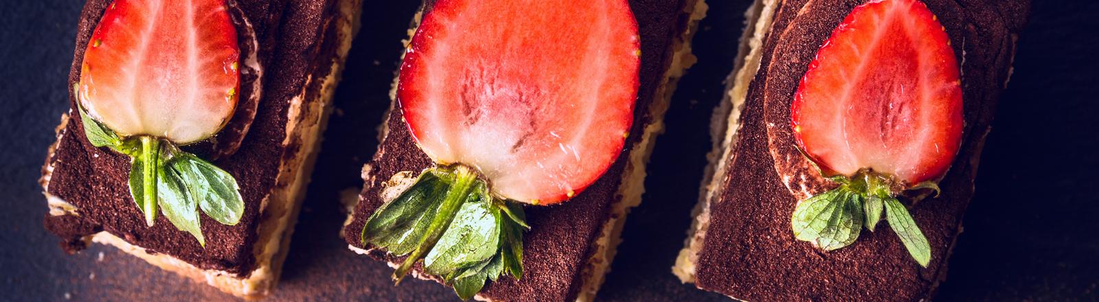 Tiramisu köstlich angerichtet mit halbierten Erdbeeren und Kakaostaub