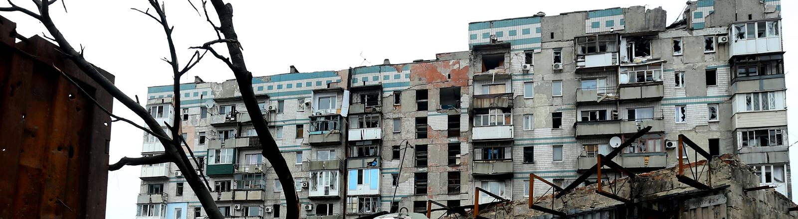 Ein Panzer steht vor einem stark beschädigten Wohnblock in der Nähe des Flughafens Donezk.