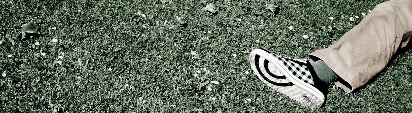 Das Bein eines Mannes, der im Gras liegt