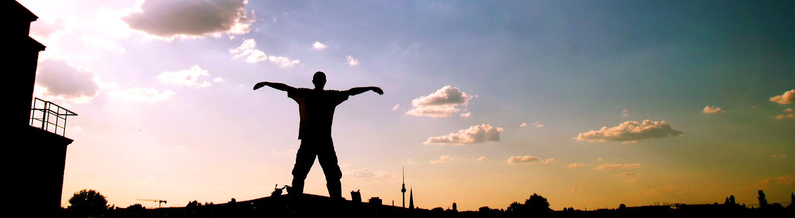 Ein Mann hat beide Arme ausgebreitet, hinter ihm ein Stadtpanorama