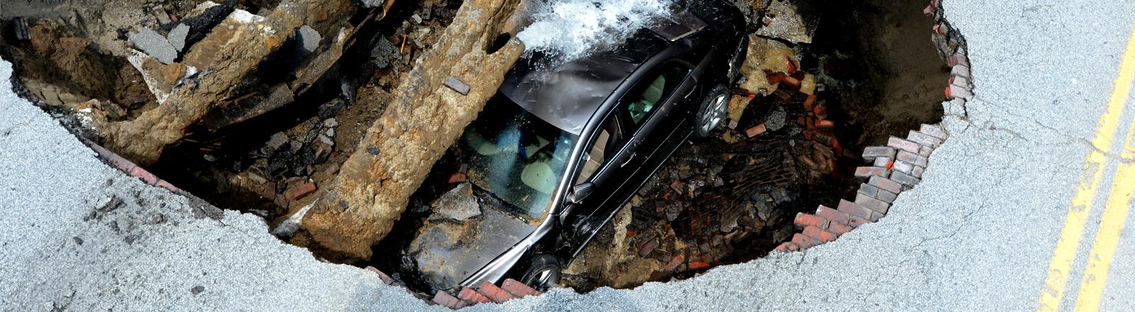In einer Straße ist ein tiefes Loch, darin sieht man ein Auto und Leitungen und Kabel, aus einer der Leitungen sprudelt Wasser.