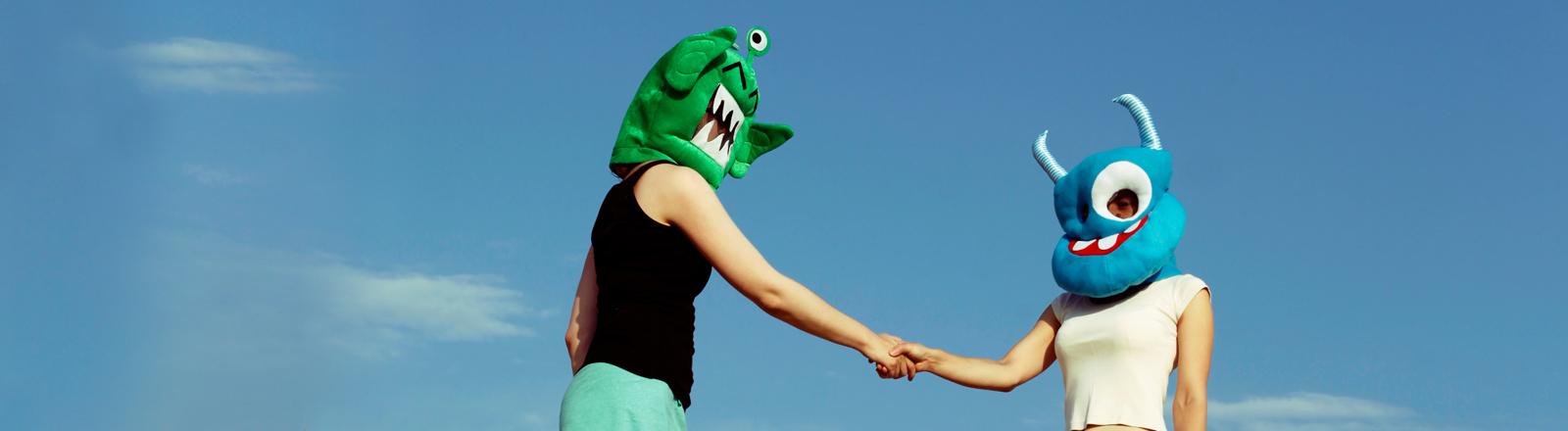 Zwei mit Alienmaske verkleidete Frauen geben sich die Hand