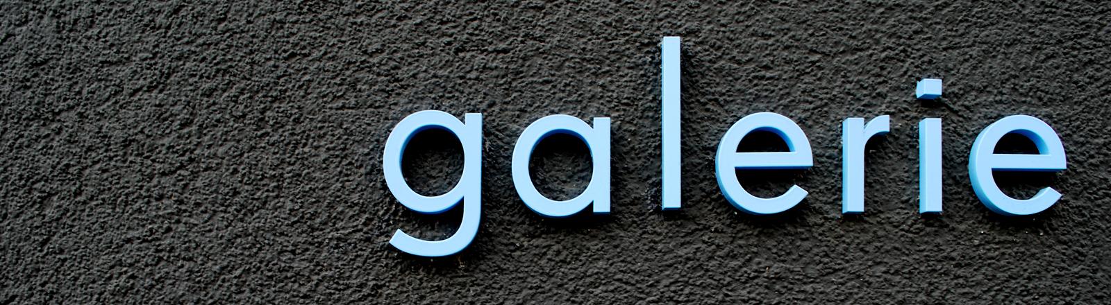 Das Wort Galerie als Leuchtschrift auf einer dunkelgrauen Wand