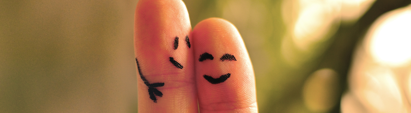 Auf Zeige- und Mittelfinger einer Hand sind Gesichter gemalt, es sieht aus, als würden sich die zwei umarmen.