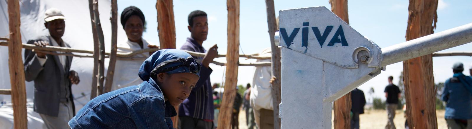 Ein kleines Mädchen steht in Afrika an einem Brunnen und füllt Trinkwasser in eine Plastikflasche.