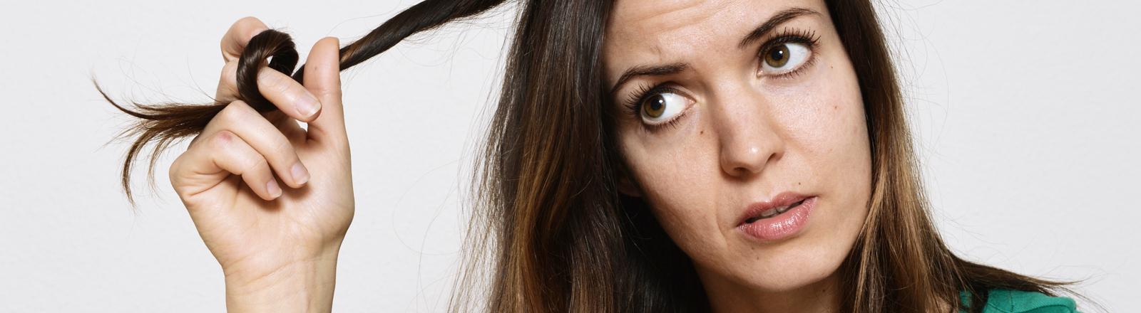 Eine Frau spielt genervt mit ihren Haaren