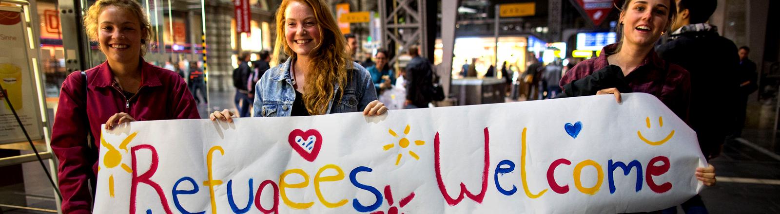 Drei Mädchen halten ein selbst gemaltes Plakat mit Herzen und Refugees Welcome Aufschrift hoch