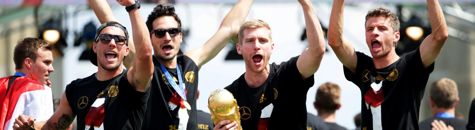 Lukas Podolski, Mats Hummels, Per Mertesacker mit WM-Pokal und Thomas Müller jubeln beim Empfang auf der Fanmeile