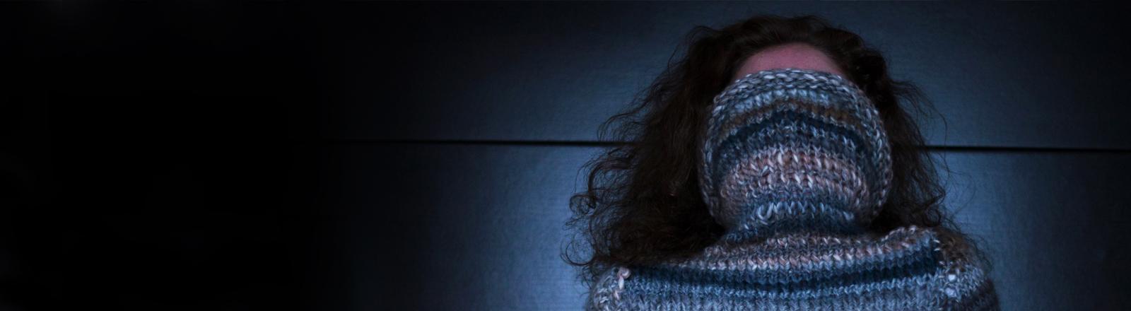 Eine Frau hat den Kragen eines Pullovers über den Kopf gezogen