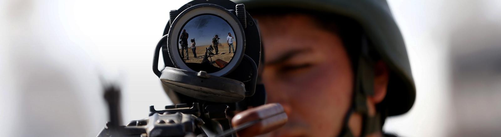 In einem Zielfernrohr auf einer Waffe spiegeln sich andere Menschen