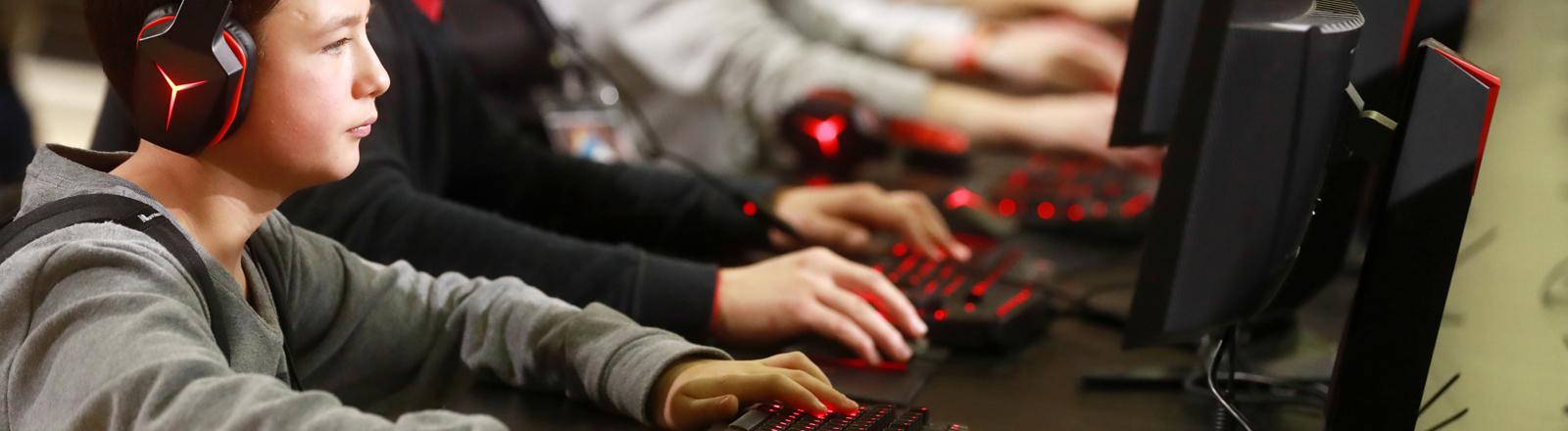 Teenager sitzen nebeneinander an Computern und spielen
