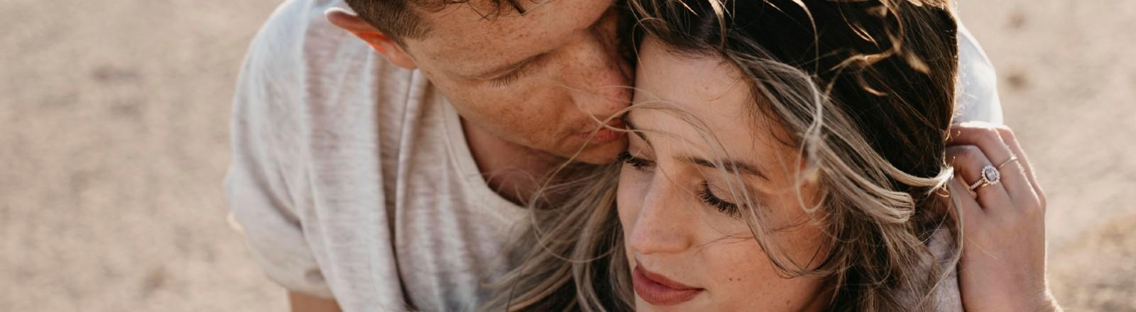 Junger Mann riecht am Kopf seiner Partnerin.