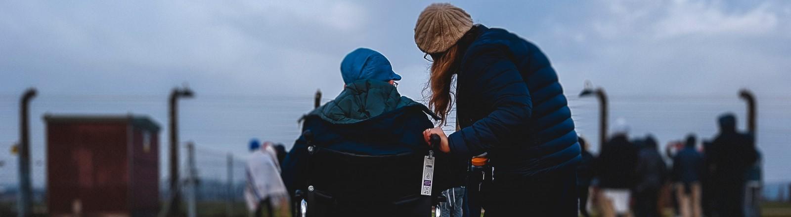 Eine Person im Rollstuhl mit einer Assistenzkraft