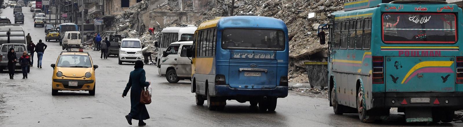 Menschen laufen am 07.02.2019 zwischen Bussen und Autos über die Straßen von Aleppo, im Hintergrund zerstörte Gebäude