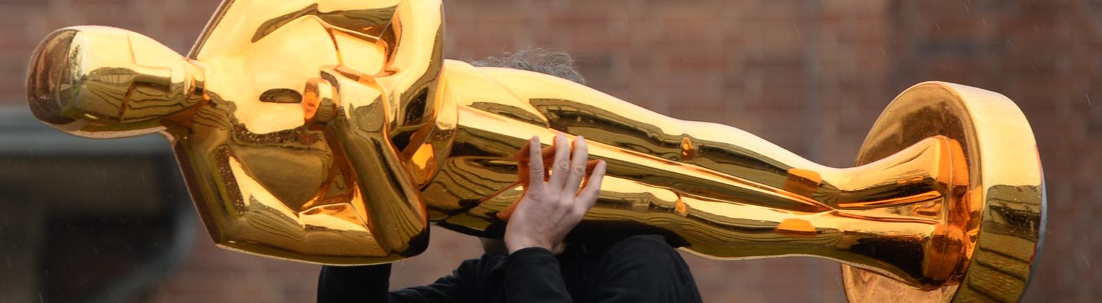 Eine lebensgroße Oscar-Statue wird von jemandem auf den Schultern durch die Gegend getragen