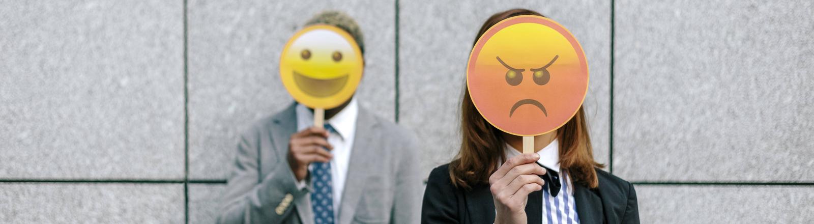 Frau und Mann halten Emoji-Schilder vor ihre Gesichter
