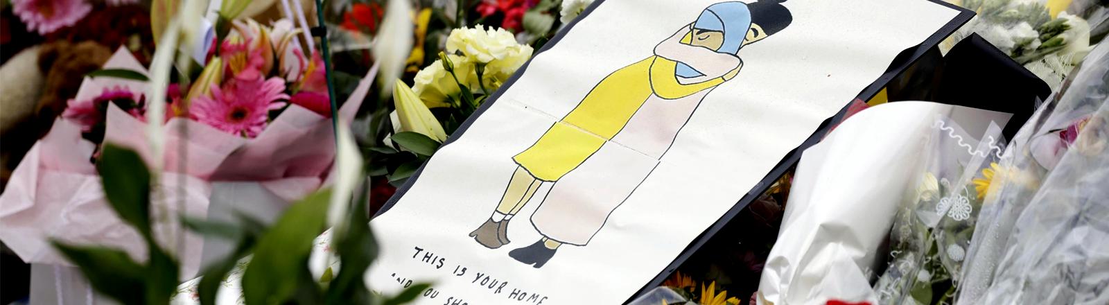 Zwischen Blumen liegt eine Zeichnung auf der sich zwei Menschen umarmen, darunter steht geschrieben: Das ist euer Zuhause, ihr hättet hier sicher sein sollen.