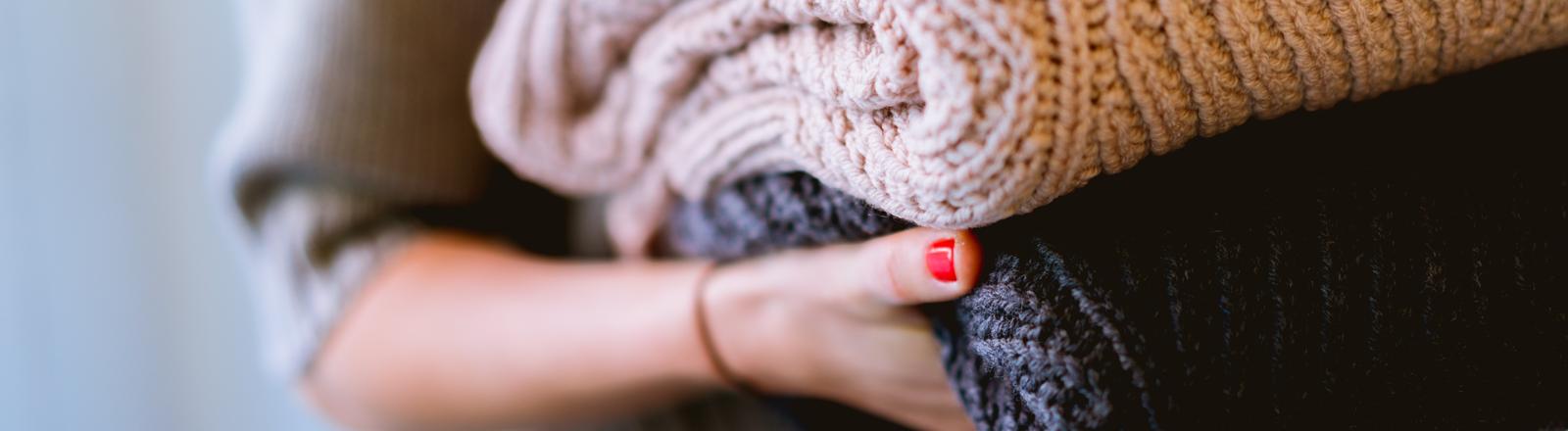 Eine Frau trägt mehrere gefaltete Pullover