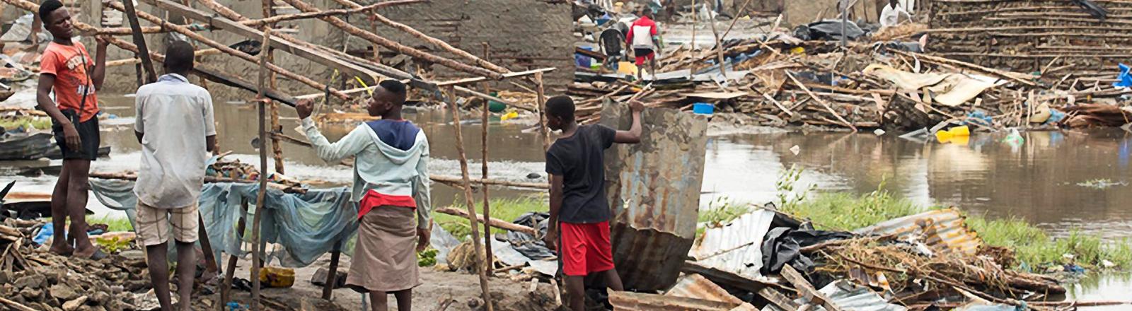 Männer stehen vor zerstörten Häusern in Beira, Mosambik und versuchen, eine Hütte zu bauen