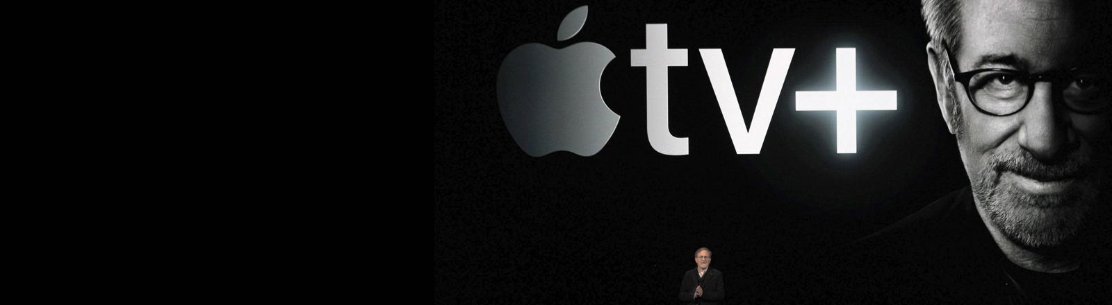 Steven Spielberg auf der Bühne der Apple-Präsentation unter einem überdimensionalen Logo für Apple TV Plus und seinem eigenen Portrait