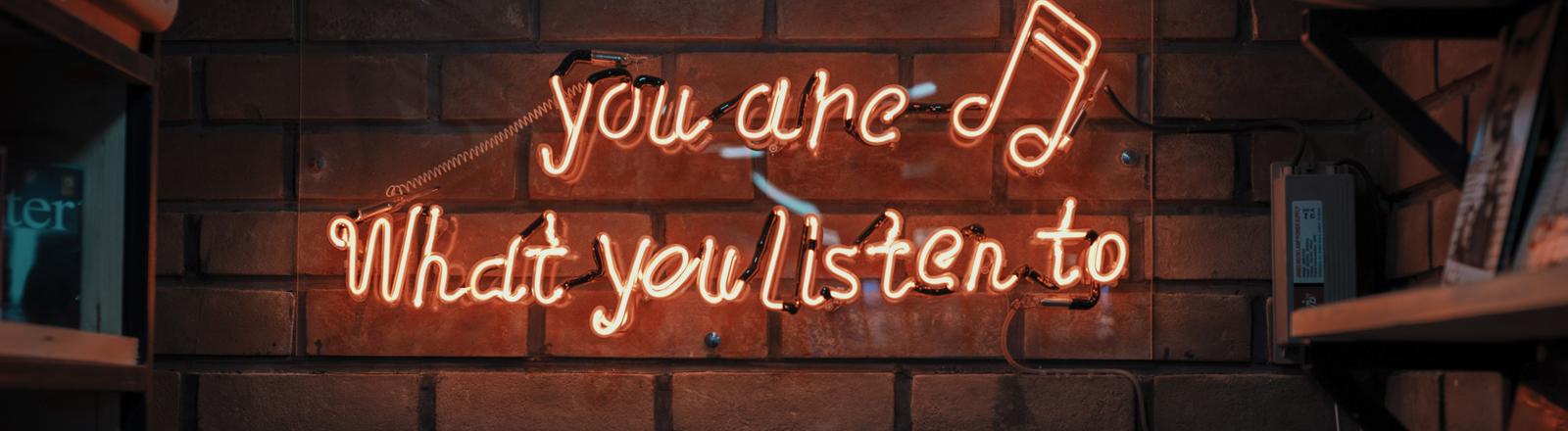Auf einer Backsteinwand ist eine Neonröhrenschrift: Du bist, was du hörst.