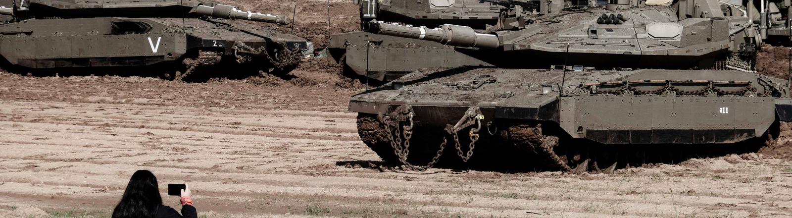 Eine Frau mit einem Smartphone in der Hand steht vor jeder Menge Panzer auf einem Acker