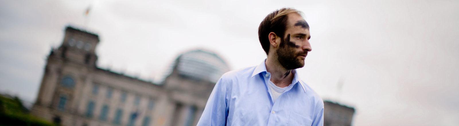 Der Aktionskünstler Philipp Ruch steht vor dem Bundestag. Sein Gesicht ist mit schwarzer Farbe beschmiert; Foto: dpa