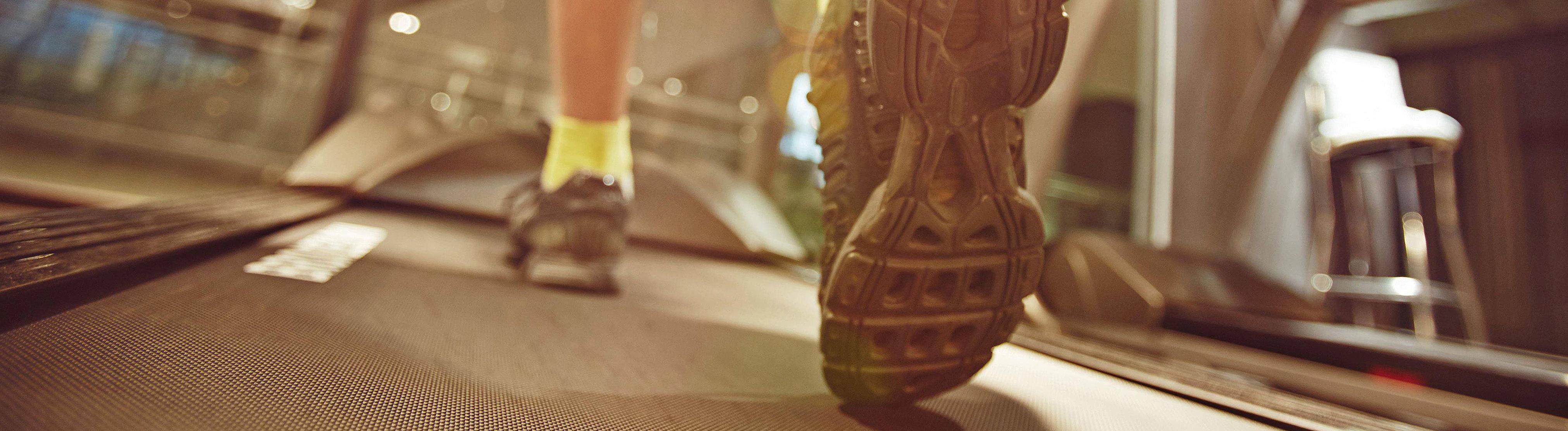 Eine Person trainiert auf einem Laufband, es sind nur das Band und die Turnschuhe zu sehen.