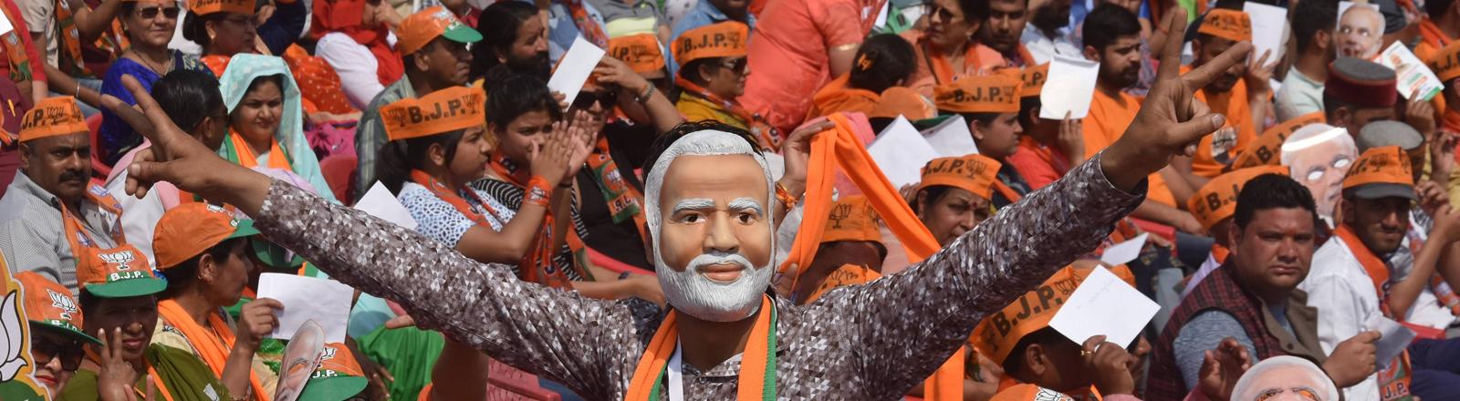 Unterstützer der BJP tragen Masken von Narendra Modi und Schals und Mützen in den Parteifarben orange und grün