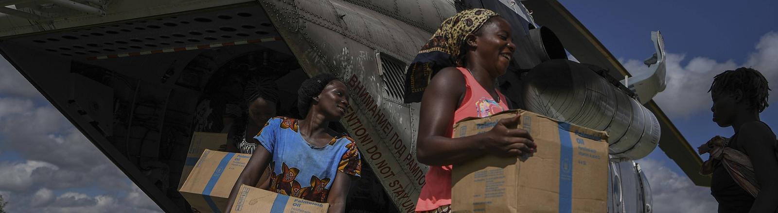 Freiwillige Helferinnen entladen in Bebedo, Mosambik einen Helikopter mit Nahrungsmitteln