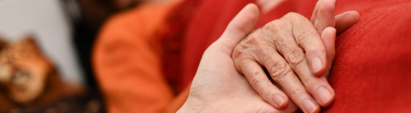 Frau hält liegender Frau die Hand.