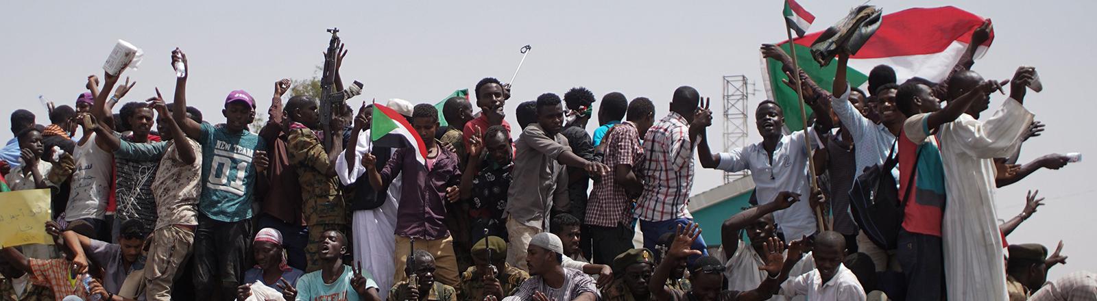 Demonstranten und Soldaten sitzen und stehen auf einem Militärfahrzeug im Sudan.