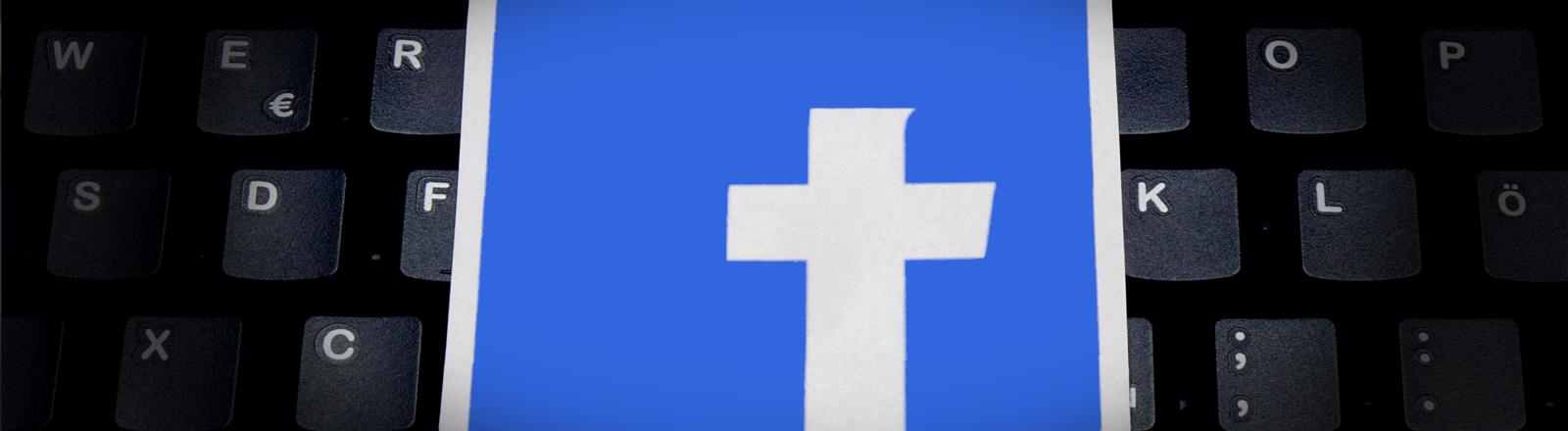 Der obere Bogen vom f des Facebook-Logos ist mit blau überdeckt, so dass ein Kreuz zurückbleibt. Das Logo liegt auf einer PC-Tastatur.