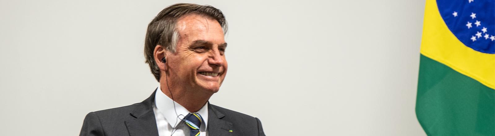 Brasiliens Präsident Jair Bolsonaro sitzt neben der brasilianischen Flagge und grinst.