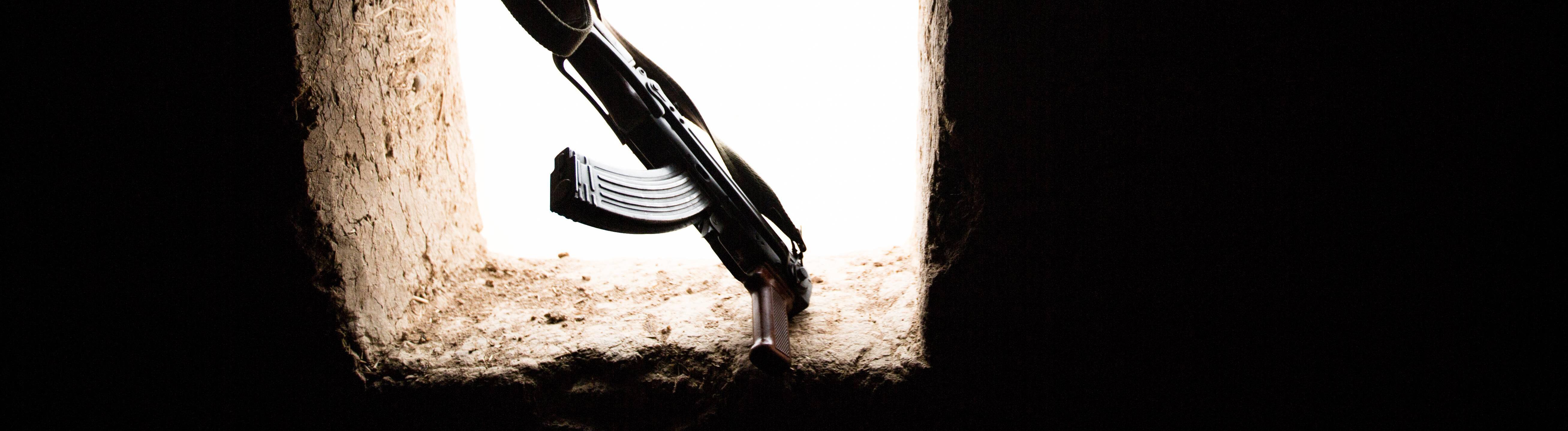 Kalaschnikow lehnt an Öffnung einer Wand