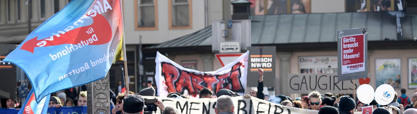10.03.2018, Sachsen, Görlitz: Teilnehmer der Kundgebung der AfD Görlitz zur Zukunft der Arbeitsplätze in der Lausitz (vorne) und Gegendemonstranten stehen sich auf dem Marienplatz gegenüber.