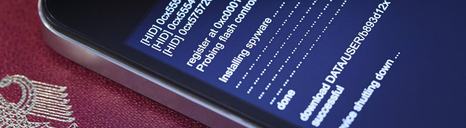 Auf einem Handy wird Spysoftware installiert.