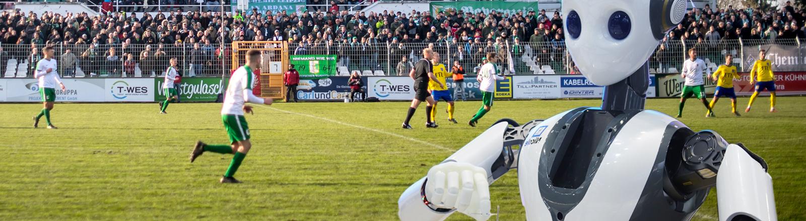Ein Roboter beobachtet ein Amateur-Fußballspiel.